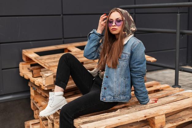 Stedelijke coole jonge stijlvolle hipster vrouw in trendy casual jeugdkleding in modieuze paarse bril poses in de stad. glamoureuze meisje mannequin zit op houten pallets in de straat. lente stijl.