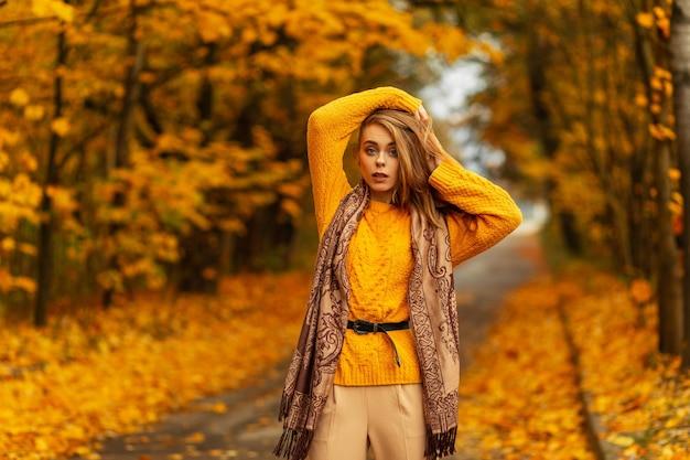 Stedelijke elegante jonge vrouw mannequin in modieuze stro witte hoed in vintage shirt rust in de stad in de buurt van modern zwart gebouw. europees fijn meisje in trendy zomerkleren buitenshuis. lieve vrouw.