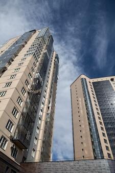 Stedelijke gebouwen met meerdere verdiepingen van baksteen en glas tegen een blauwe hemel