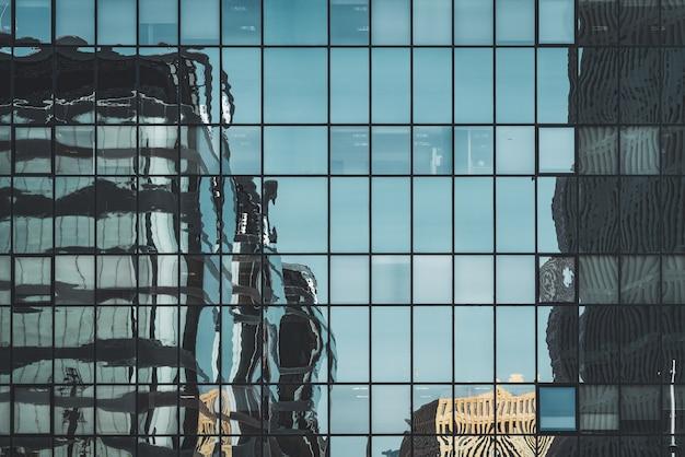 Stedelijke gebouwen weerspiegeld op een glazen gevel