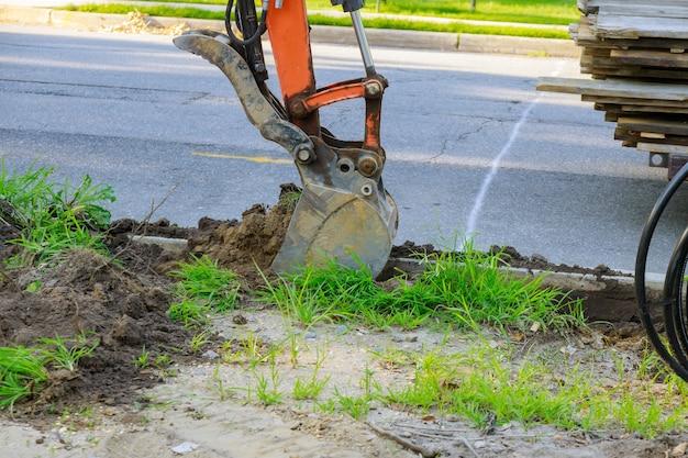 Stedelijke gemeentelijke tractor met pollepel graaft het riool op grondwerken.