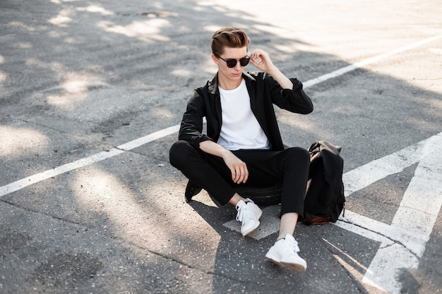 Stedelijke jonge hipster man met kapsel in zonnebril in een zwart shirt in trendy gestreepte broek in sneakers met een rugzak zitten op straat