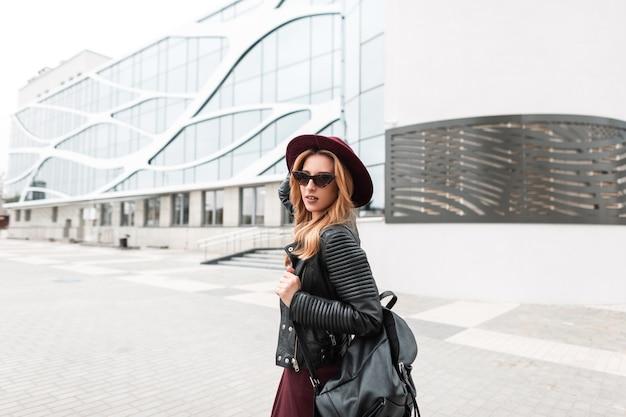 Stedelijke jonge hipster vrouw in trendy zonnebril in een vintage paarse hoed in een leren jas met een zwarte stijlvolle rugzak
