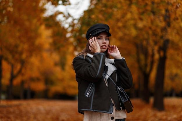 Stedelijke jonge vrouw in een bruin warm jasje in een elegante hoed met een vizier met een vintage leerzak poseren in het park. europese meisjesmannequin in modieuze herfstkleren buitenshuis. jeugdstijl.