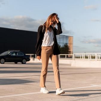 Stedelijke jonge vrouw in zwarte jas in vintage broek in fashion zonnebril in sexy top loopt op asfalt en maakt haar recht. mooi meisje loopt in de parkeergarage van de stad op een zonnige, heldere zomerdag.