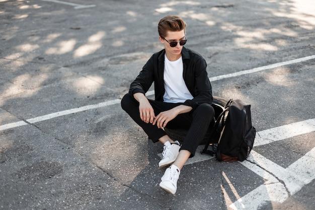 Stedelijke jongeman hipster met kapsel in zonnebril in elegante modieuze kleding in witte sneakers rusten in de stad