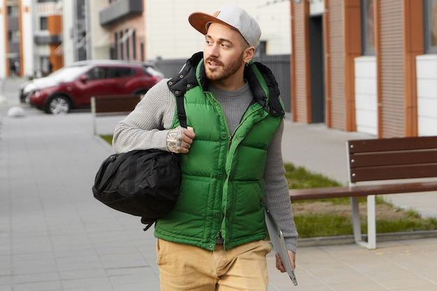 Stedelijke levensstijl, technologie en reisconcept. aantrekkelijke modieuze jonge europese man met stoppels stijlvolle kleding dragen, met zwarte schoudertas en digitale tablet, op zakenreis