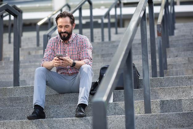 Stedelijke levensstijl. vrolijke aangename man met behulp van zijn telefoon zittend op de trap buiten