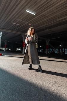 Stedelijke mode mooie krullende vrouw in vintage lange jas met stijlvolle tas wandelingen in de stad. vrouwelijke casual stijl en schoonheid