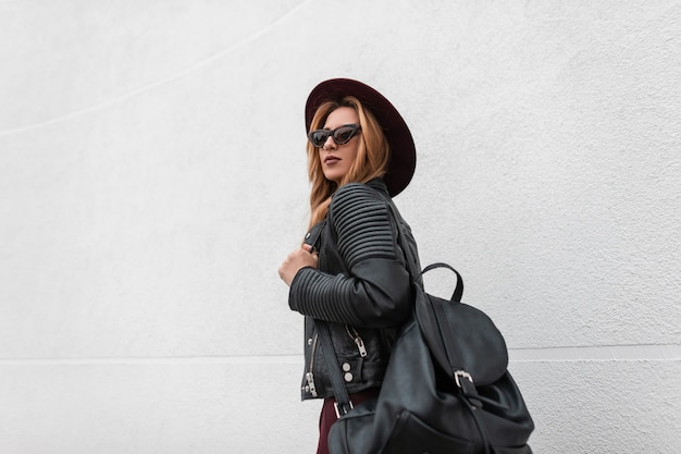 Stedelijke mooie jonge hipster vrouw in trendy donkere zonnebril in een chique hoed in een leren jas met een zwarte stijlvolle rugzak