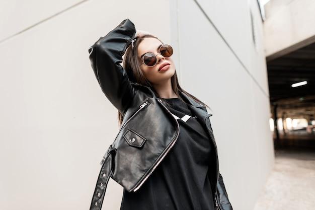 Stedelijke mooie jonge hipster vrouw met stijlvolle ronde zonnebril in een mode leren jas met een zwart sweatshirt loopt door de stad