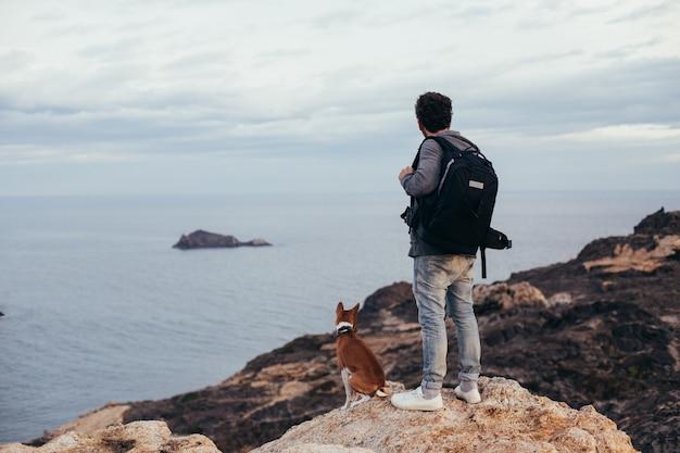 Stedelijke ontdekkingsreiziger of avonturier staat op de top van de berg met beste vriend