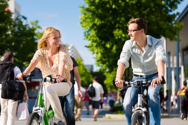 Stedelijke paar berijdende fiets in vrije tijd in stad