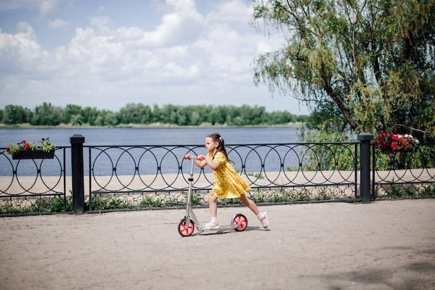 Stedelijke sport- en gezinsactiviteiten een meisje rijdt snel op een scooter een meisje op een scooter op de dijk...