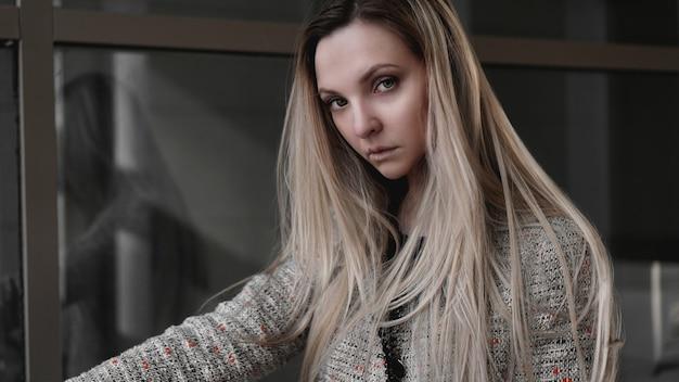 Stedelijke stijl blond meisje met een strenge blik staande op de achtergrond van een modern gebouw. girl power en bedrijfsconcept.