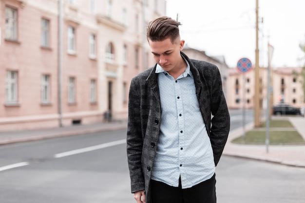 Stedelijke stijlvolle jonge kerel met trendy kapsel in modieuze elegante kleding in de buurt van vintage huizen buitenshuis.