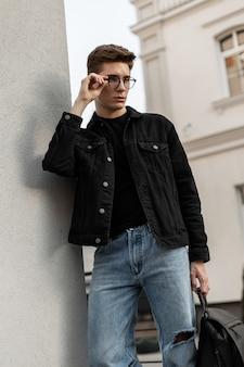 Stedelijke stijlvolle jongeman in denim zwarte jas in spijkerbroek met leren rugzak staat in de buurt van vintage muur en rechtzetten bril. europese knappe man mannequin in modieuze vrijetijdskleding.