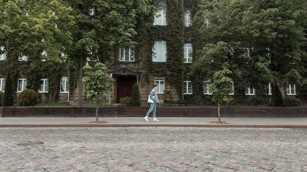 Stedelijke stijlvolle jongeman toerist in trendy jeugdjeans kleding met modieuze stoffen tas reist op vintage stadsstraat in de buurt van oud gebouw begroeid met groene bladeren. moderne modeman houdt van wandelen.