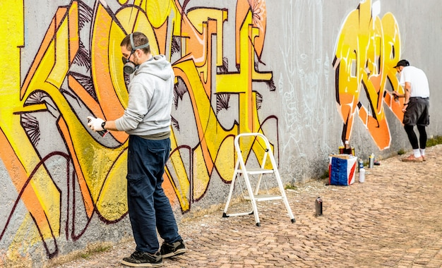 Stedelijke straatkunstenaar die kleurrijke graffiti schildert