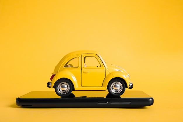 Stedelijke taxi mobiele online applicatie concept. speelgoed gele taxi automodel. hand met slimme telefoon met taxi service app tentoongesteld.