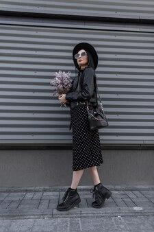 Stedelijke vrouw brunette in elegante hoed in zonnebril in zwarte jeugd jurk staat met boeket van lila bloemen in de buurt van metalen vintage muur buitenshuis. stijlvol meisje geniet van wandelen en verse mooie bloemen.