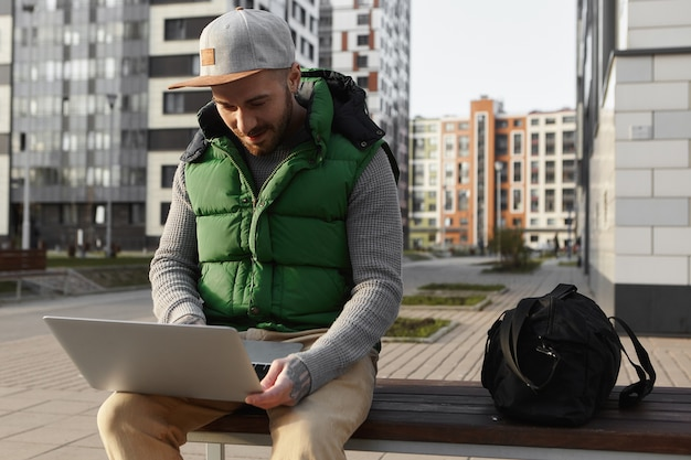 Stedelijke weergave van stijlvolle jonge ongeschoren man nieuws lezen, e-mail controleren of bericht online typen met behulp van draagbare computer buitenshuis, zittend op een bankje met tas, alleen reizen, genieten van gratis wifi