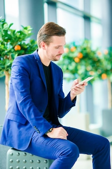 Stedelijke zakenman die op slimme telefoon binnen in luchthaven spreekt. toevallige jonge jongen die jasje draagt. blanke man met mobiel op de luchthaven tijdens het wachten op instappen