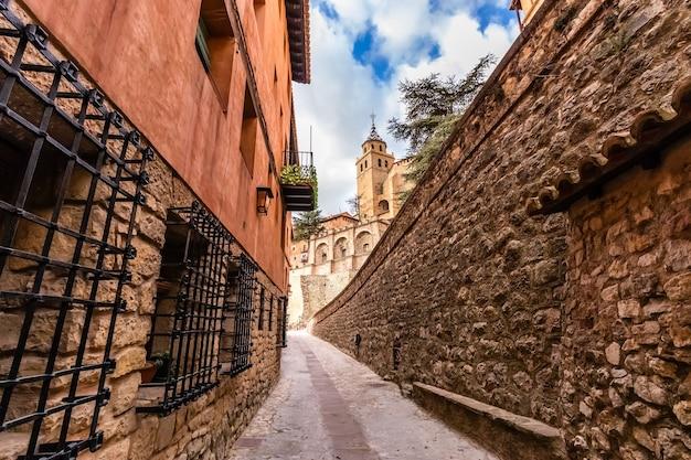 Steegje tussen stenen muren en getraliede ramen die naar de kathedraal van de stad leiden. albarracãn teruel spanje. aragon