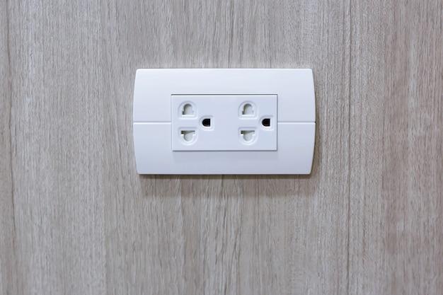 Steek de stekker in het stopcontact sluit de stopcontacten op de houten muur aan. stopcontacten stopcontacten met 220 volt (220v) ac-stijl.