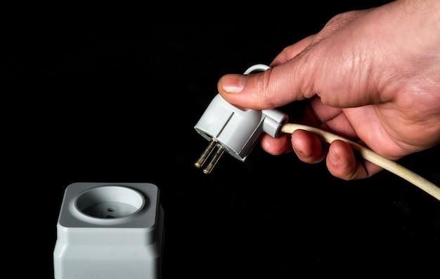 Steek het netsnoer handmatig in een wit plastic of europees stopcontact.