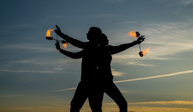 Steek je dansende vlam aan. dansend paar draait brandende poi. vlamdansers op idyllische hemel. avond tinten en lichten. brand prestaties. openluchtfestival. nacht feestje. plezier en vermaak.