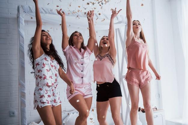 Steek uw handen zo hoog mogelijk op confetti in de lucht. jonge meisjes hebben plezier op het witte bed in een mooie kamer
