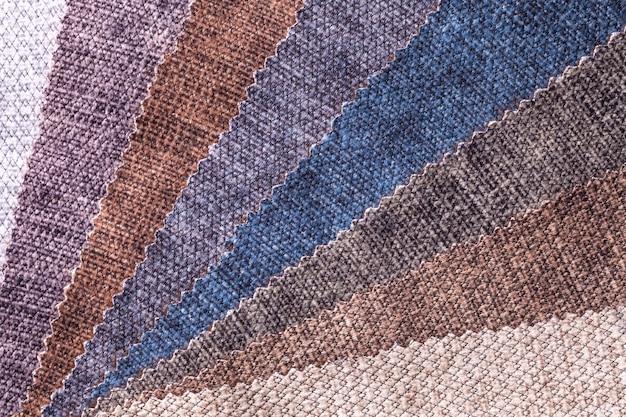Steekproef van fluweel textiel bruine en grijze kleuren, achtergrond. catalogus van interieurstoffen voor meubels. velours veelkleurige stof.