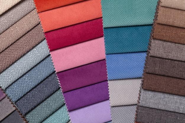 Steekproef van geweven textiel verschillende kleuren, achtergrond. catalogus en palettoon van interieurstof voor meubels, close-up. verzameling van veelkleurige stof met rieten patroon.
