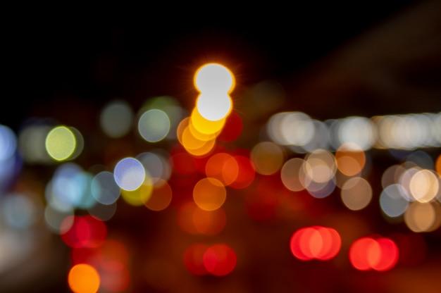 Steekt vage lichten aan van auto's op de weg die als achtergrond wordt gebruikt.
