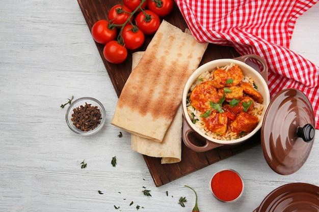 Steelpan met heerlijke kip tikka masala en rijst op tafel