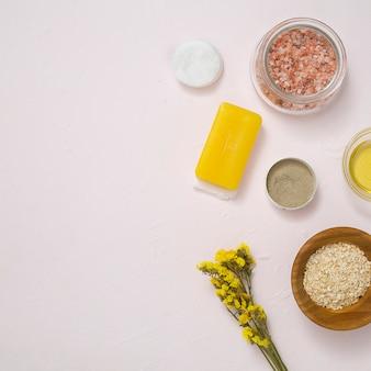 Steen zout; wattenschijfjes; zeep; haver; gele limoniumbloem en schoonheidsmiddelenproducten op witte concrete oppervlakte
