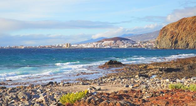 Steenachtig strand en de steden las americas en los cristianos op de achtergrond, het eiland tenerife, canarische eilanden