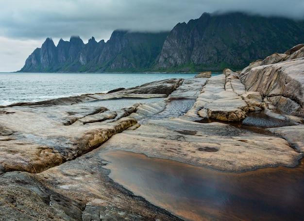 Steenachtig strand met getijdenbaden in ersfjord, senja, noorwegen. zomer polaire dag nacht kust. de drakentanden schommelen in de verte.