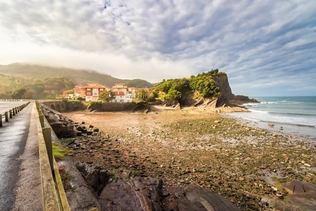 Steenachtig strand met huizen aan zee, kliffen en dramatische hemel met stapelwolken. vizcaya, baskenland. spanje