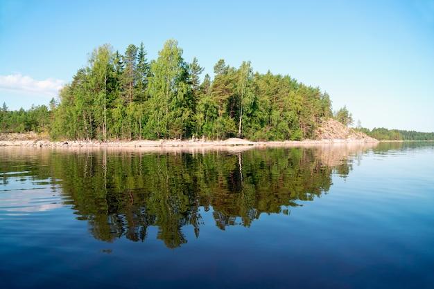 Steeneiland met een weerspiegeling in het water op het meer