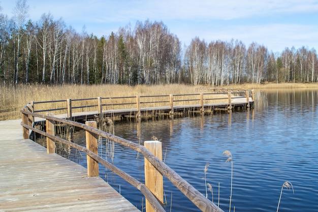 Steengroeve in olaine, letland. houten pad langs het meer. oever van het meer, riet en pad