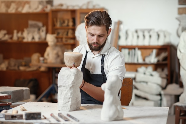 Steenhouwer werkt met houten hamer en beitel op kalksteen.