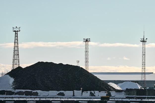 Steenkoolhoop, natuurlijke zwarte steenkool, mijnbouwproduct en drie torens met zoeklichten. industrieel landschap met stapel koolstofmateriaal. opwarming van de aarde, co2-uitstoot, steenkoolenergie