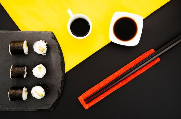 Steenplaat met sushibroodjes en kom met sojasaus op een zwarte achtergrond met eetstokjes