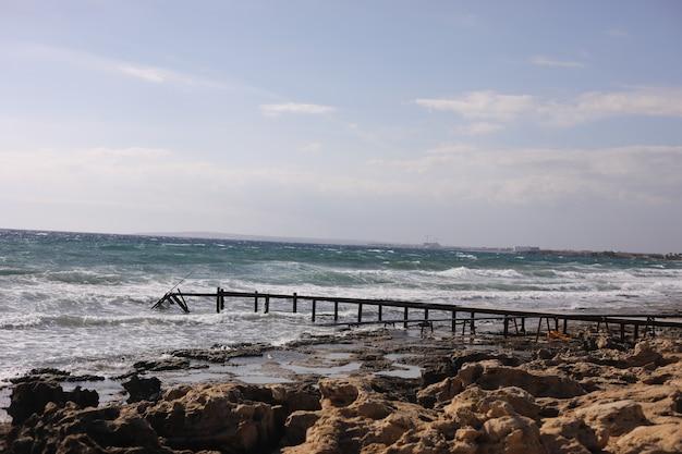 Steenstrand met oud houten ponton dichtbij de overzeese achtergrond. selectieve aandacht