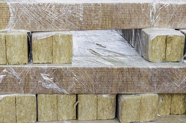 Steenwol op een bouwplaats. detailopname. minerale wol gevouwen op een pallet in cellofaanverpakking.