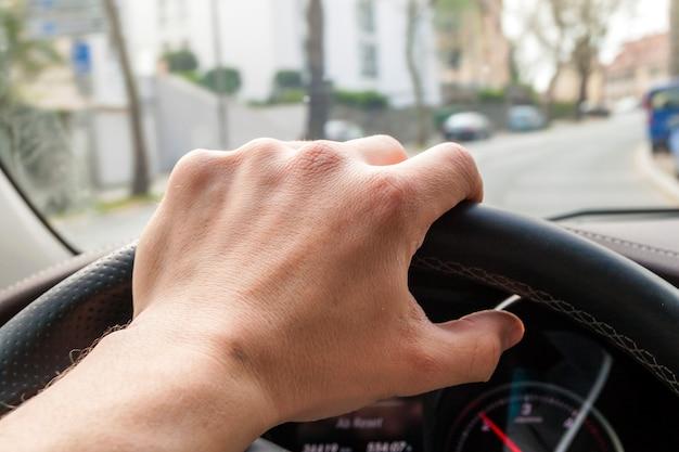 Steerind wiel met bestuurder hand op in moderne auto-interieur met uitzicht op straat