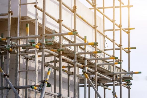 Steigerbuisklem en onderdelen, bouwplaats met steigertoren en gebouw