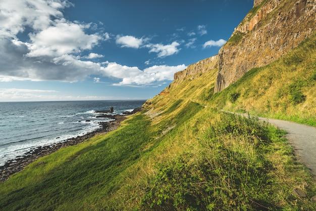 Steile groene helling met toeristische pad. ierland.